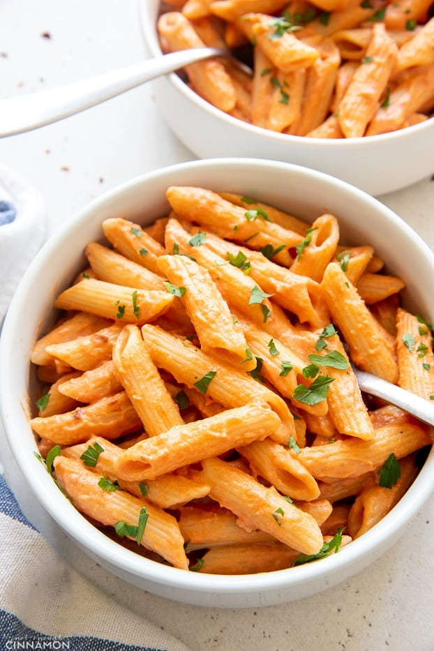 close-up of a bowl of vegan penne vodka sprinkled with parsley