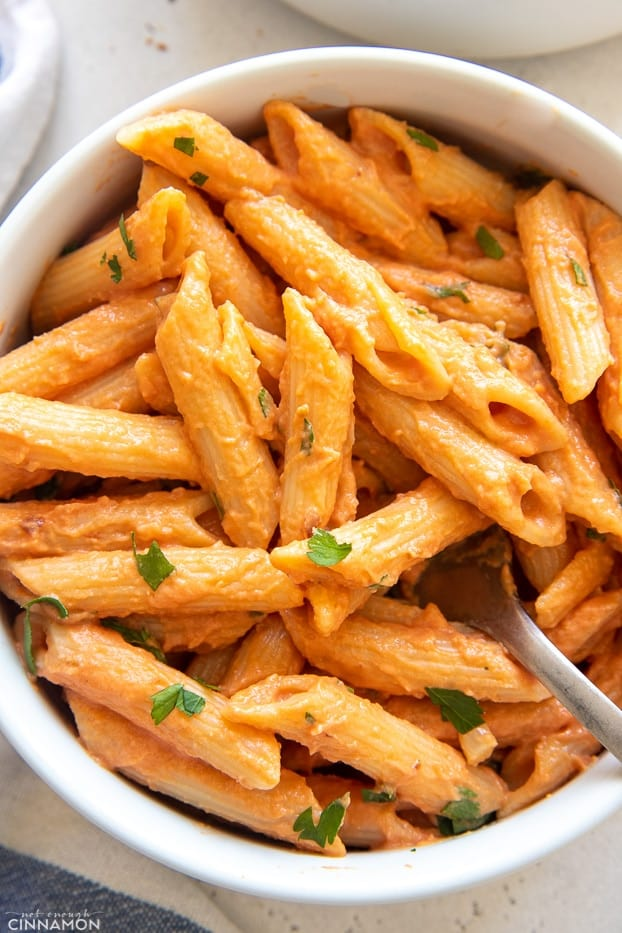 overhead shot of a bowl of vegan dairy free penne vodka in a white bowl