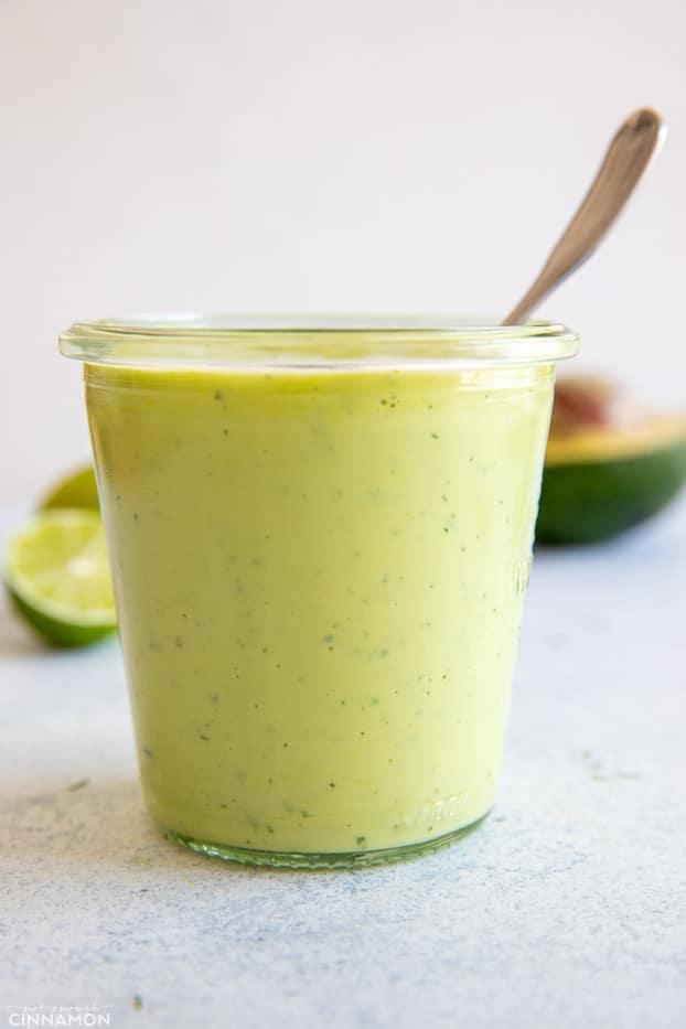 side view of vegan avocado ranch dressing in a small mason jar