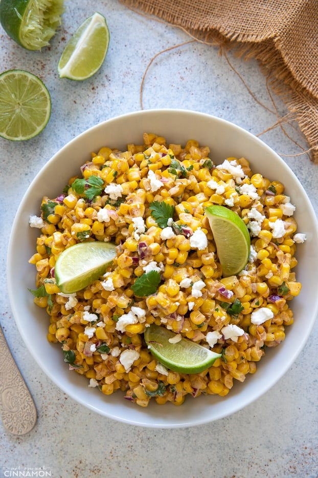 overhead shot of a bowl of Mexican Street Corn Salad with cotija cheese and lime wedges