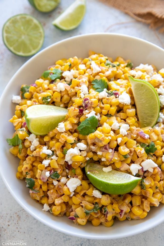 side view of a bowl of healthy Mexican Street Corn salad with lime wedges and cotija cheese