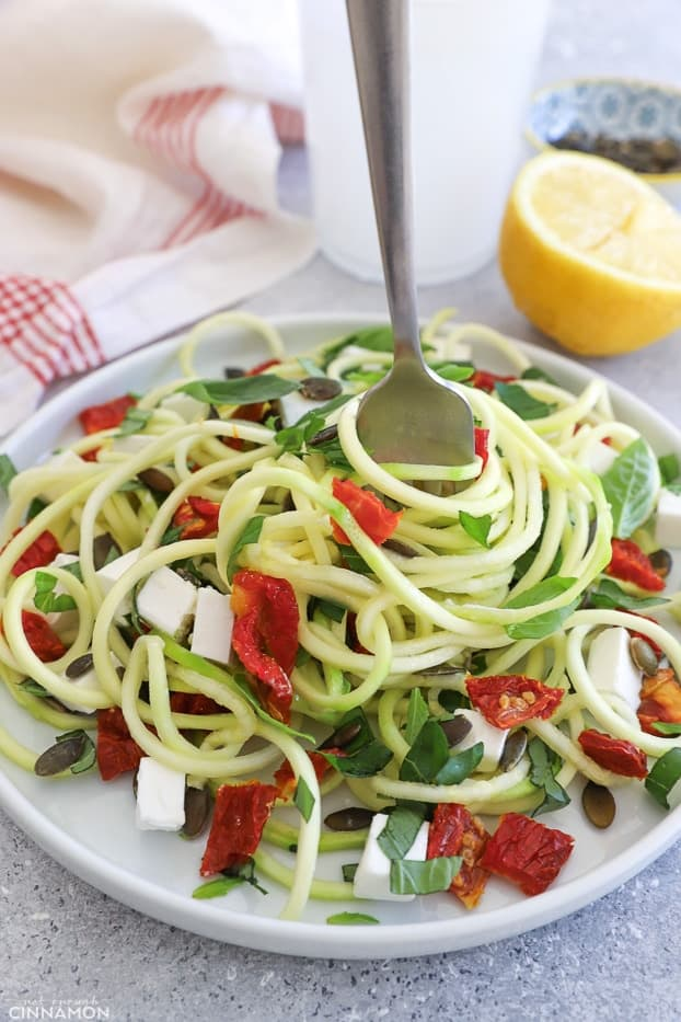 a plate of Mediterranean spiralized zucchini salad with a fork twirling the noodles