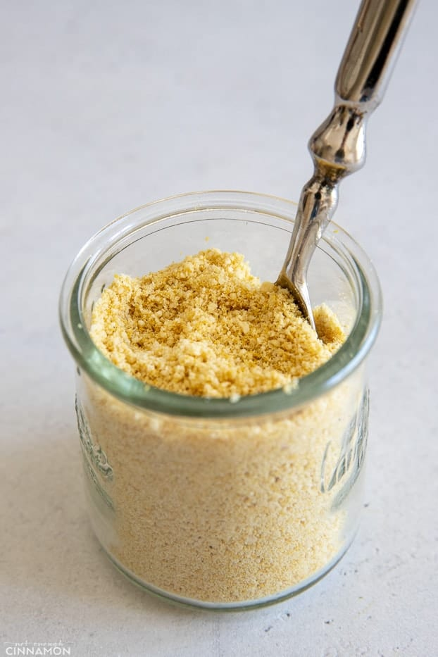 side view of a small glass jar filled with vegan parmesan cheese