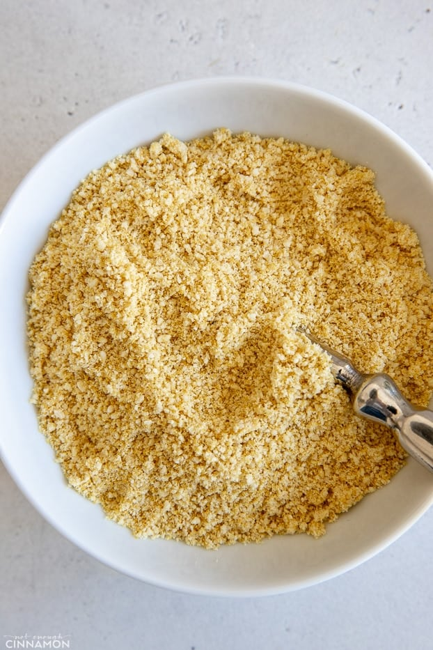overhead shot of a white bowl filled with vegan parmesan cheese