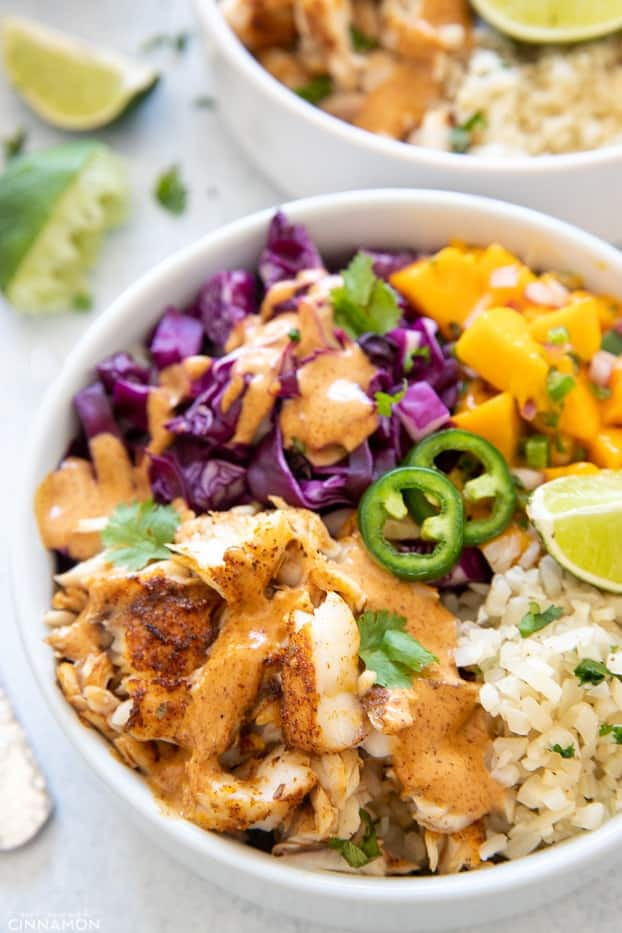 side view of a healthy fish taco bowl with mango salsa and cilantro lime cauliflower rice