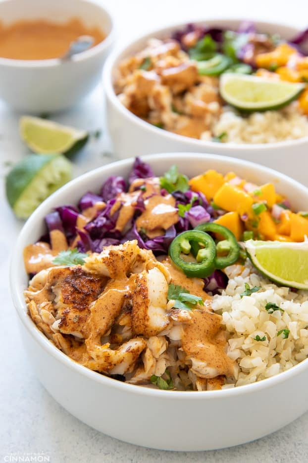 side view of a healthy fish taco bowl with cilantro lime cauliflower rice and baked fish fillet drizzled with chipotle mayo
