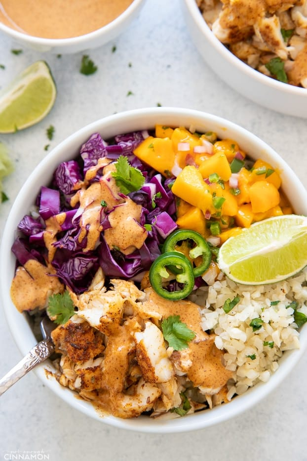 overhead shot of a healthy whole30 fish taco bowl with cauliflower rice and chipotle mayo