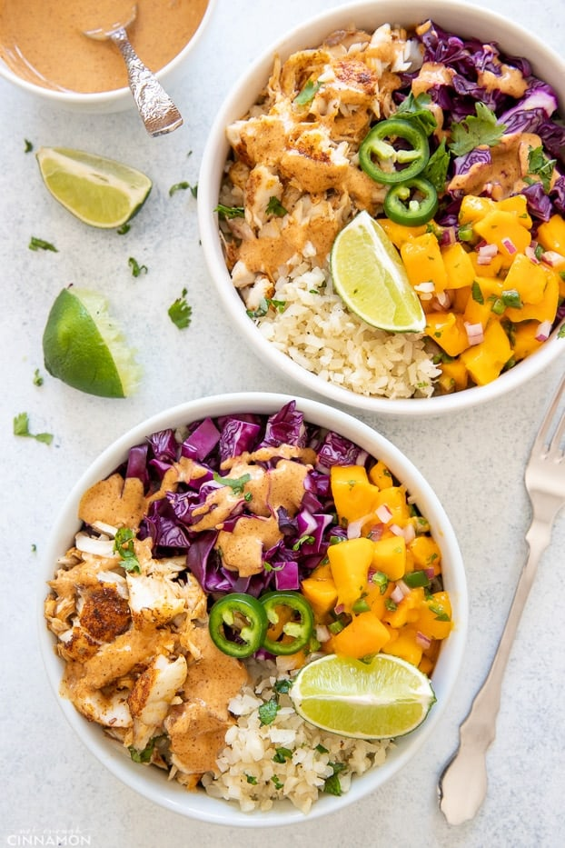 overhead shot of two healthy fish taco bowls with baked white fish, mango salsa, slaw and cauliflower rice