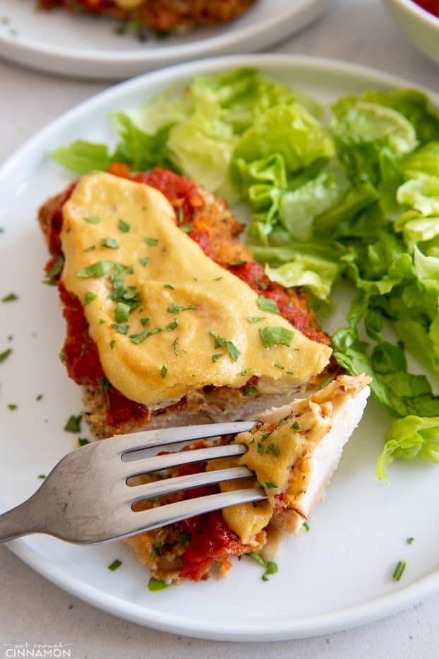 a fork piercing into a piece of homemade chicken parmesan