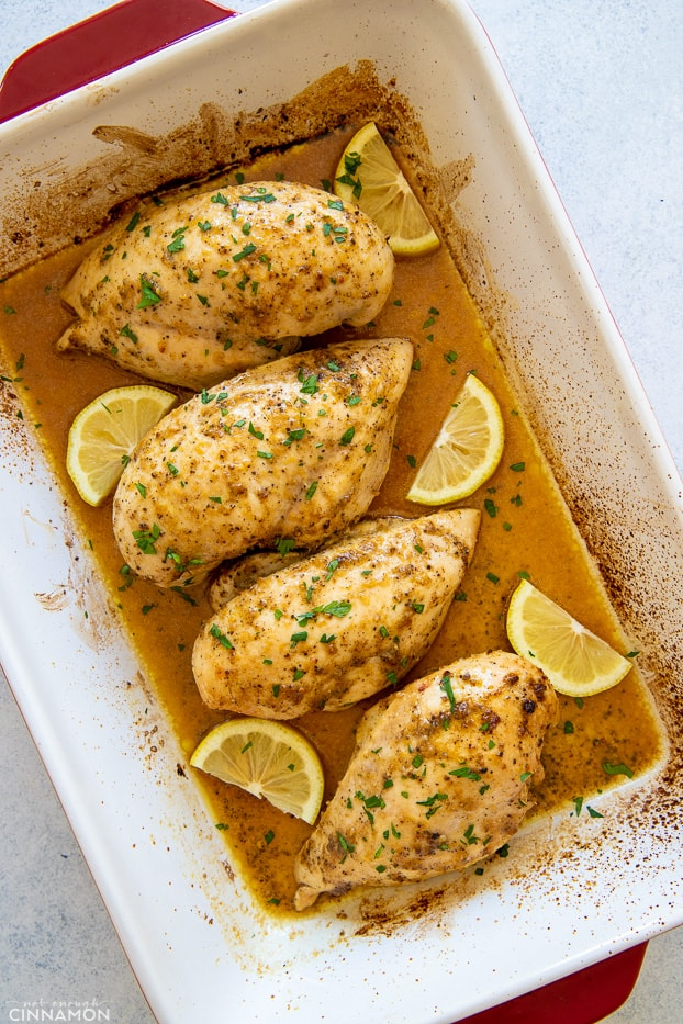 overhead shot of baked lemon pepper chicken breast in a white casserole