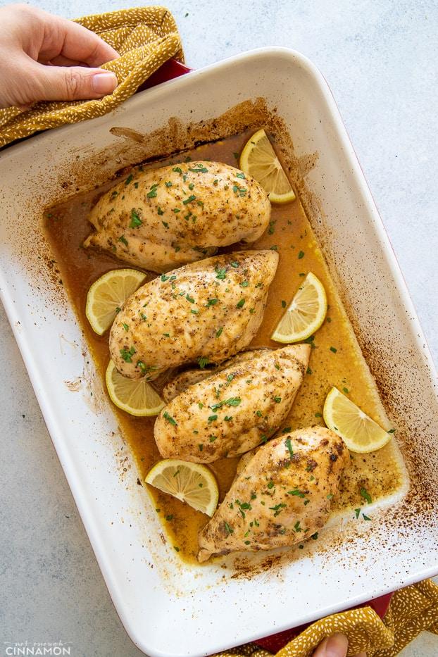 overhead shot of baked lemon pepper chicken in a white casserole dish