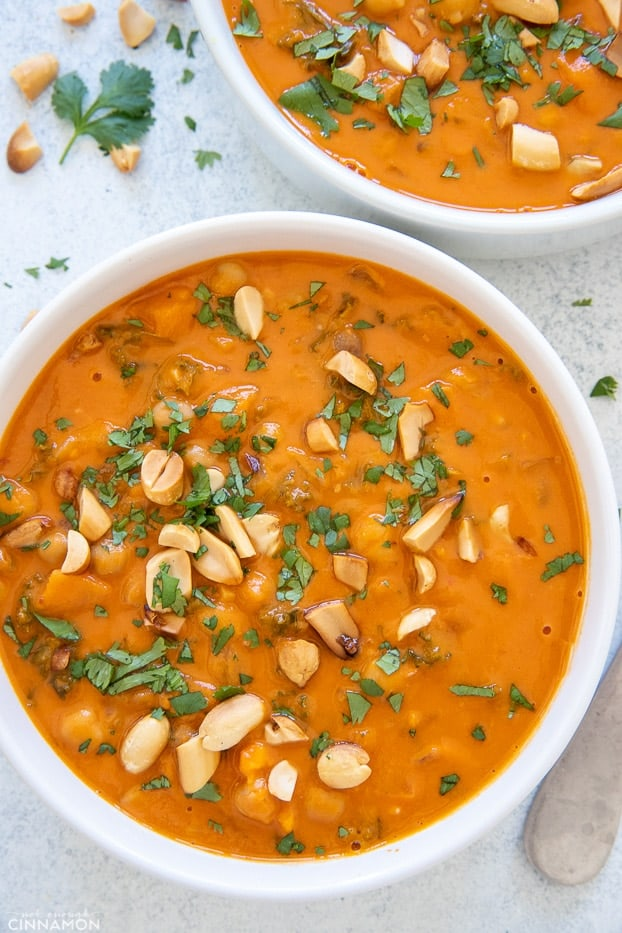 overhead shot of a bowl of West African Peanut Soup sprinkled with peanuts and cilantro
