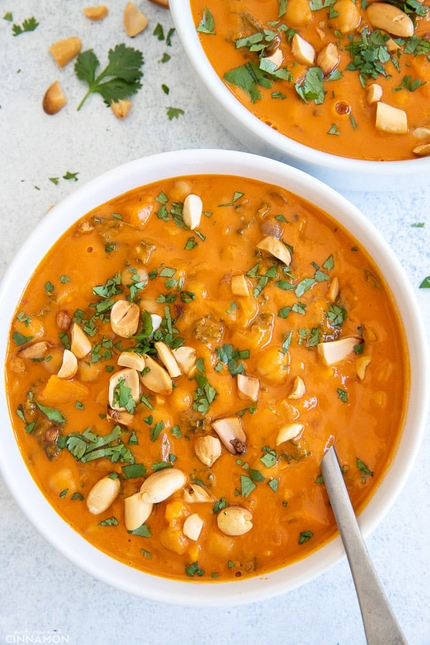 a bowl of African Peanut Soup with chickpeas and vegetables with a soup spoon inserted