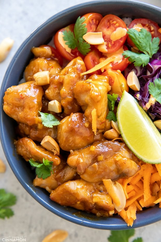 overhead shot of a Thai peanut butter chicken bowl served with chopped peanuts and lime wedges