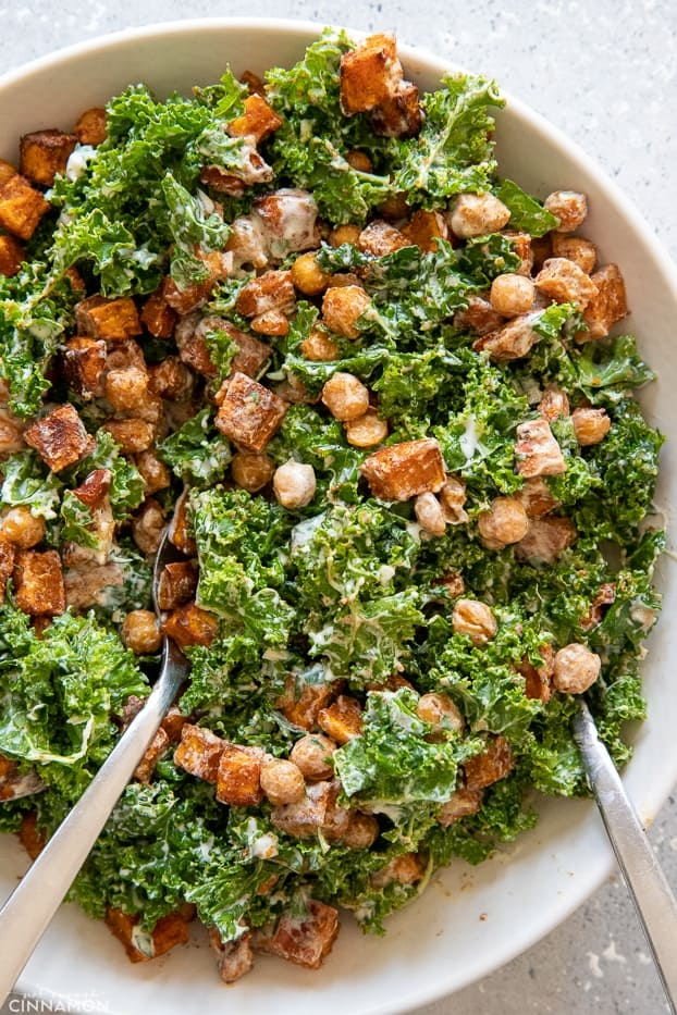 roasted chickpea sweet potato salad with kale being tossed with creamy Greek yogurt dressing