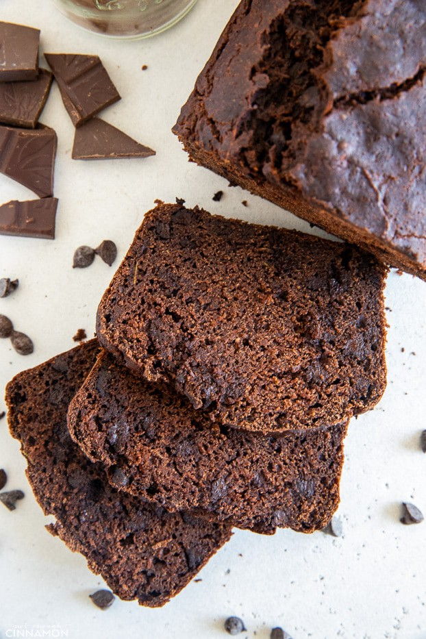 three slices of moist gluten-free chocolate zucchini bread surrounded by chocolate chips