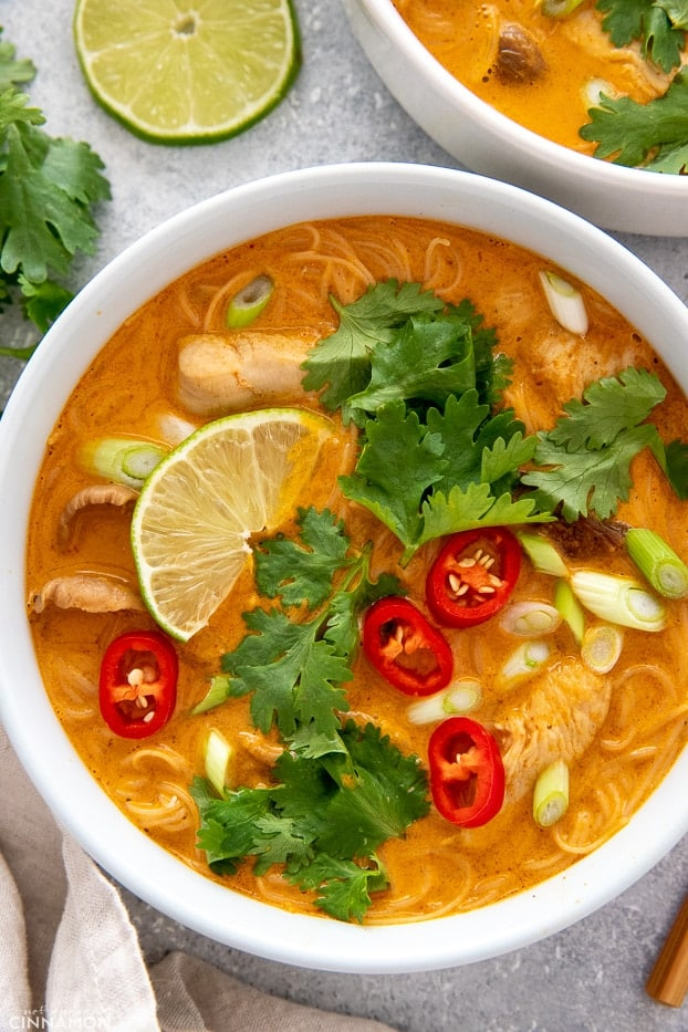 overhead shot of a bowl of Asian Thai Curry Noodle Soup decorated with lime cilantro and chile