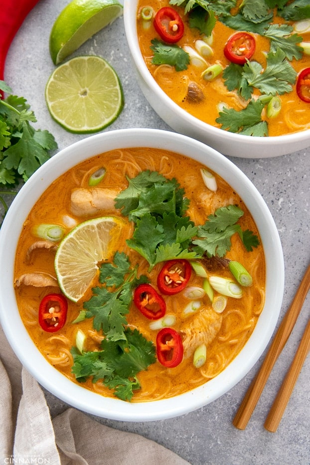 two white bowls with Red Curry Thai Noodle Soup with Chicken and Coconut Milk