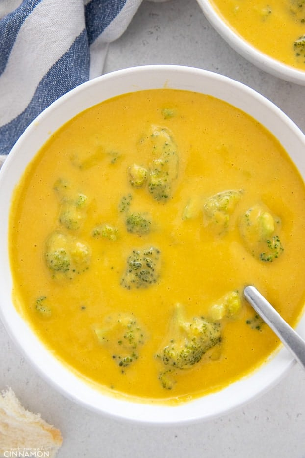 a bowl with vegan broccoli cheese soup with a spoon