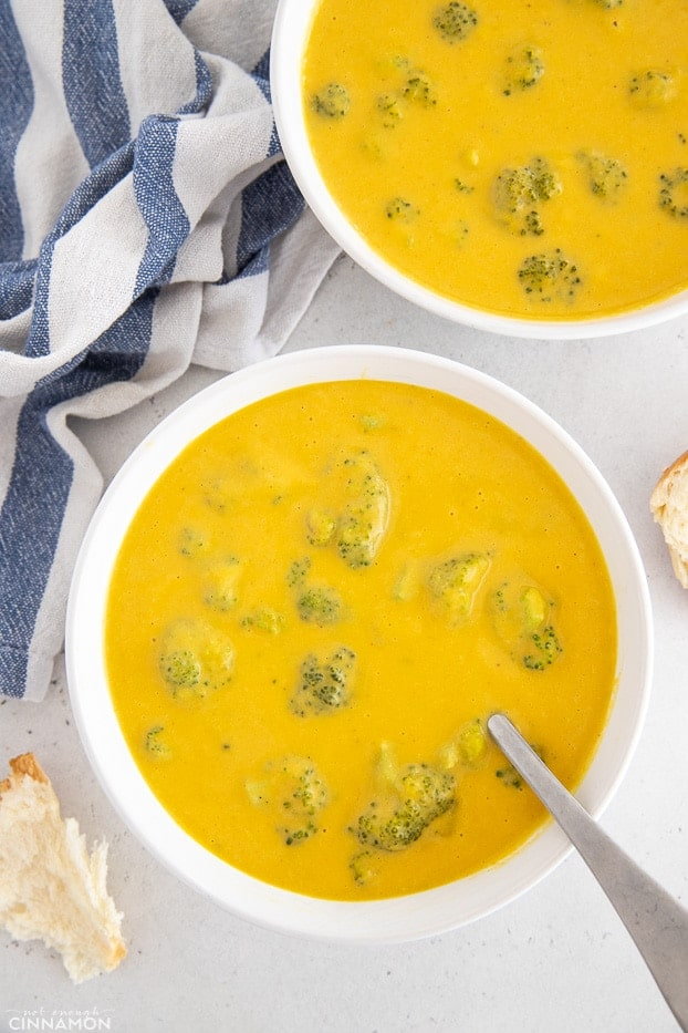 overhead shot of two bowls of vegan broccoli cheese soup