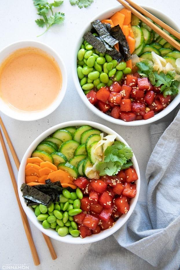 overhead shot of two vegan poke bowls with watermelon tuna served with sriracha mayo