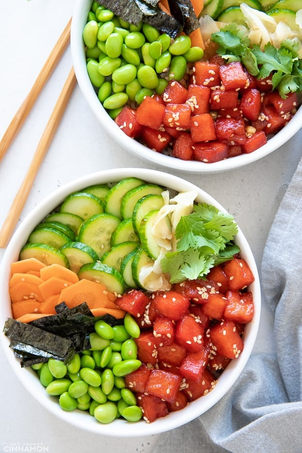 overhead shot of two watermelon tuna vegan poke bowls with chopsticks on the side