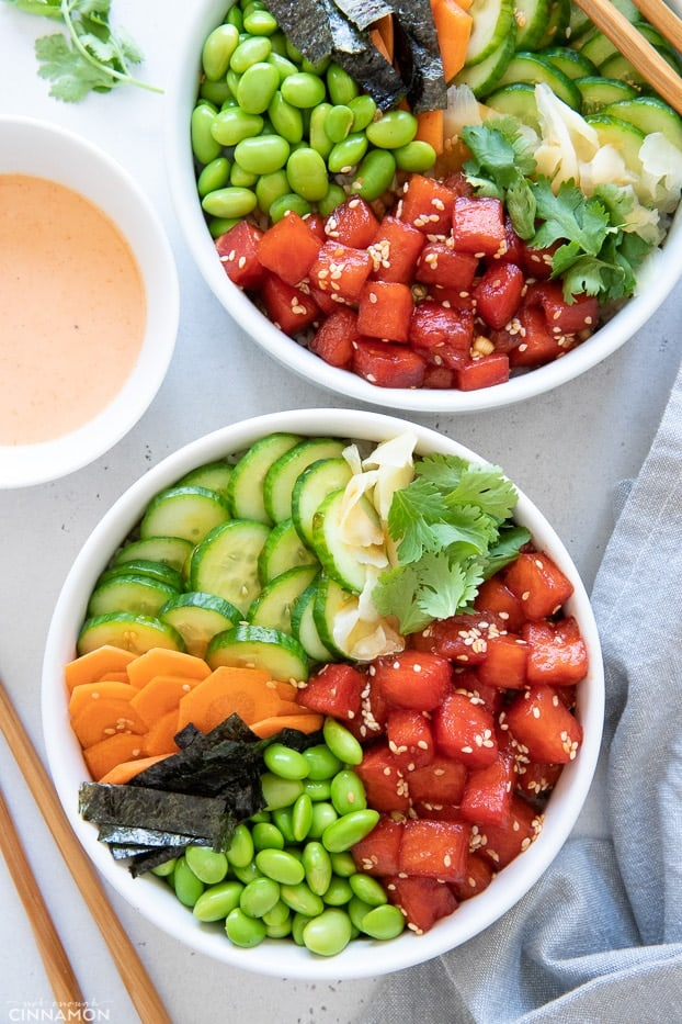 overhead shot of two vegan watermelon tuna poke bowls with cucumber, nori and edamame