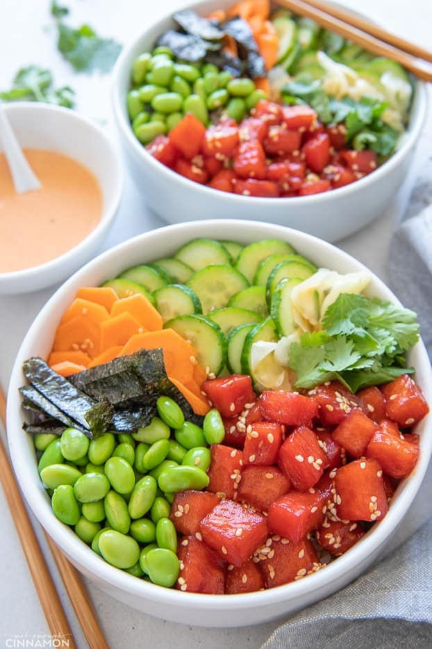 two vegan poke bowls with edamame beans, nori and watermelon tuna served with a side dish of mayo