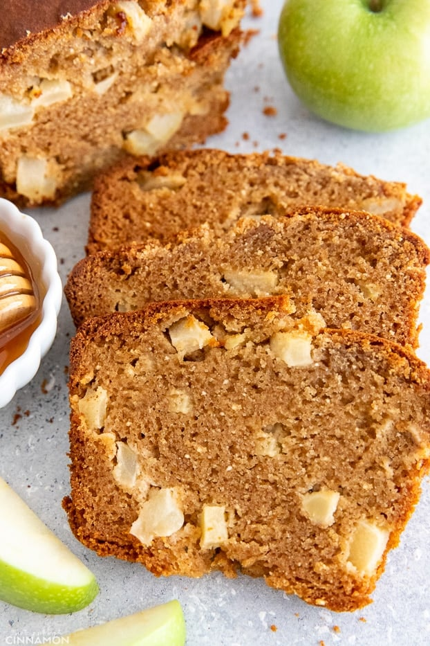 sliced loaf of Paleo Honey Apple Bread with honey and apple slices on the side