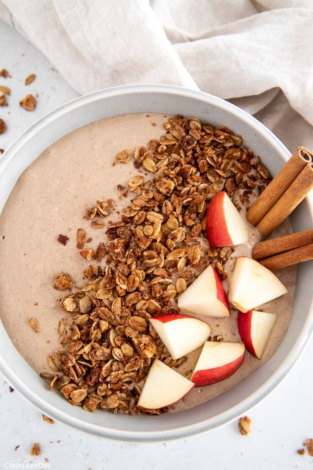 overhead shot of a healthy vegan apple pie smoothie bowl topped with cinnamon sticks granola and apples