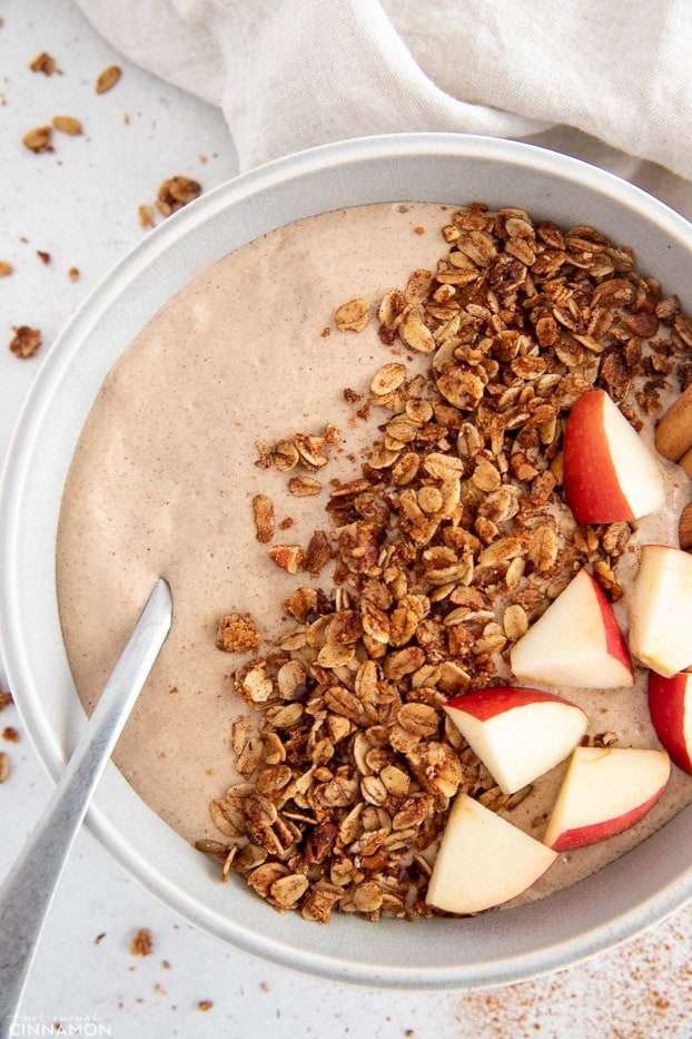 overhead shot of a apple pie smoothie bowl topped with fruit and granola