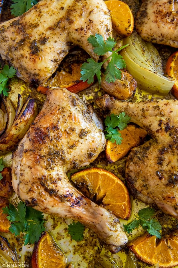 tender juicy chicken pieces roasting on a sheet pan along with orange slices