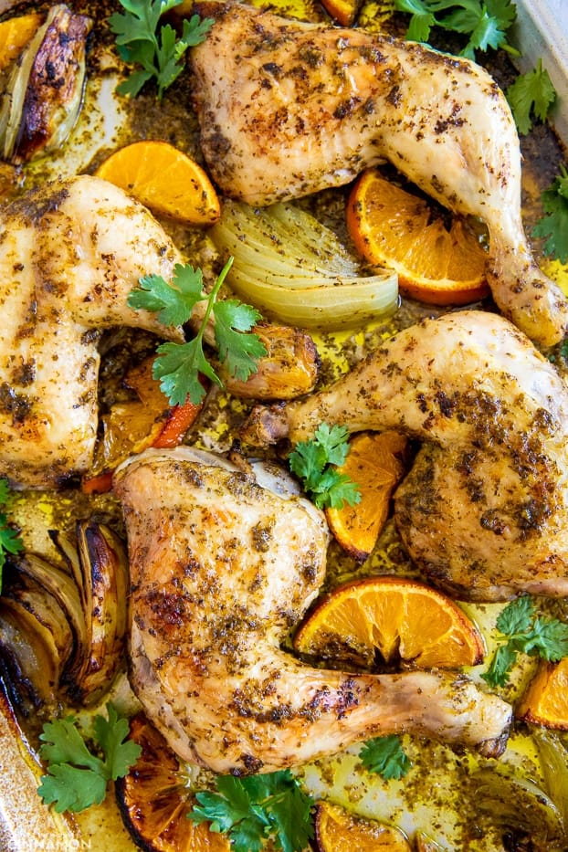 Roasted Chicken pieces in Mojo marinade on a baking sheet