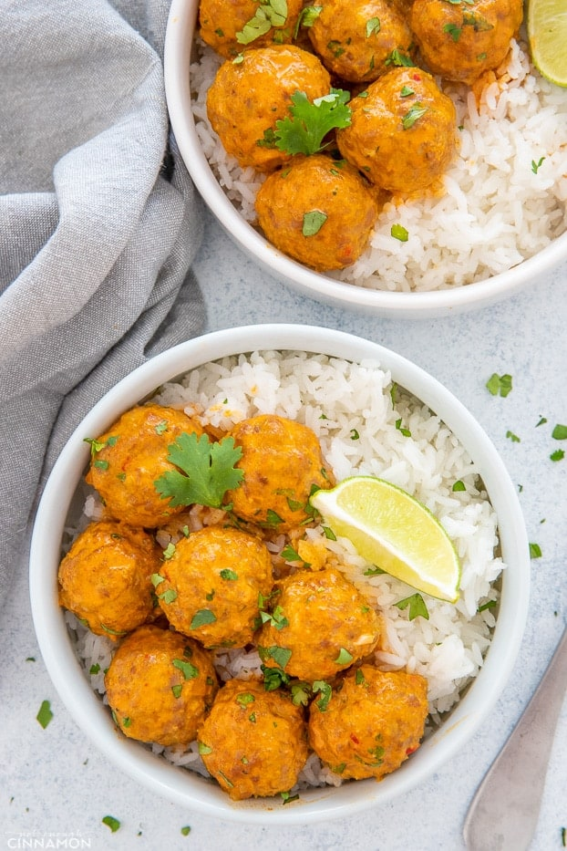 thai coconut meatballs curry served with rice and lime wedges