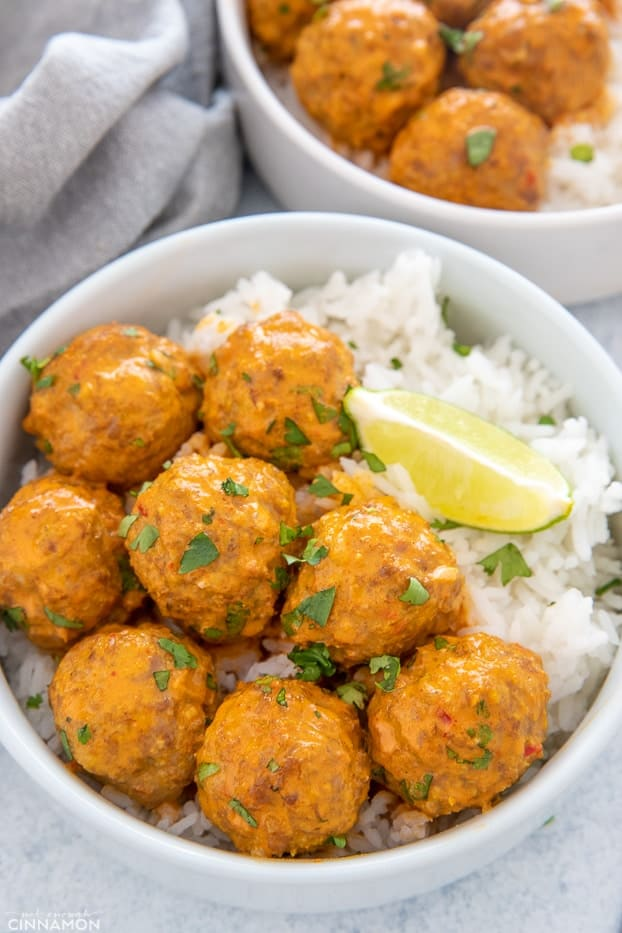 close-up of a serving of thai turkey meatballs served with a side of rice and lime wedges