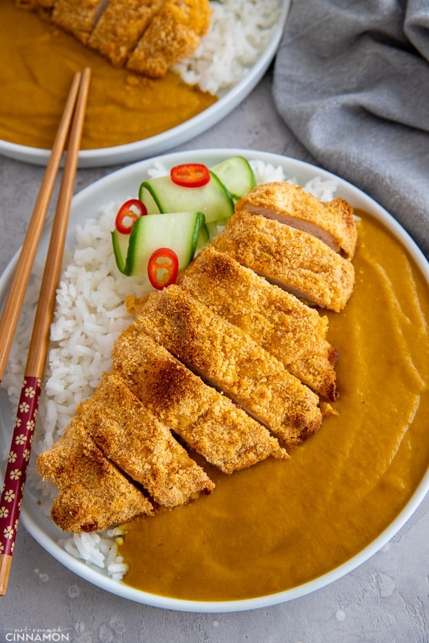 a serving of healthy paleo chicken katsu curry served with cucumber and a mild curry sauce