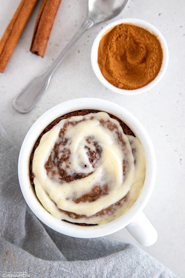 overhead shot of healthy cinnamon roll mug cake with cream cheese frosting