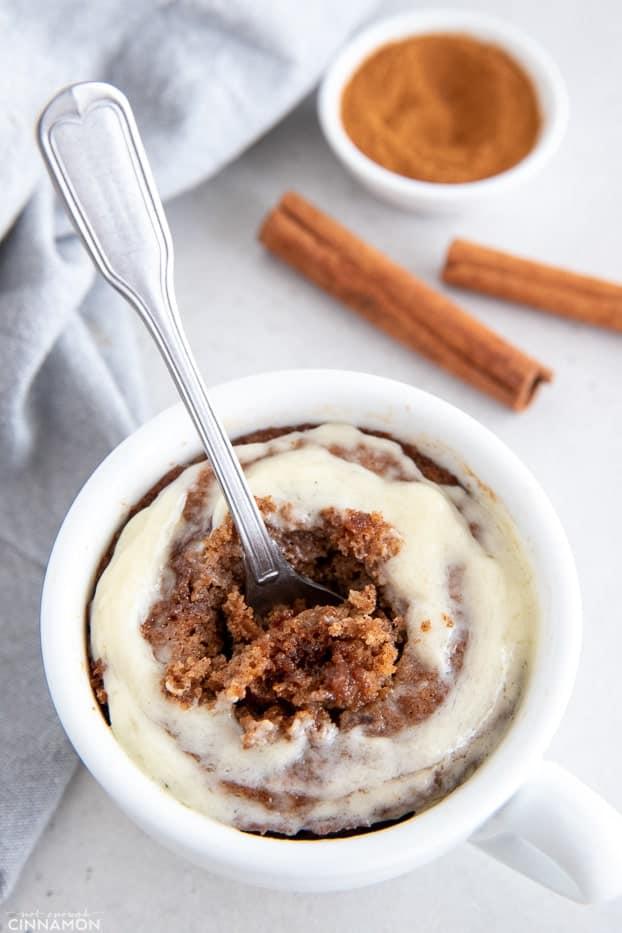 a spoon being dug into a mug with healthy cinnamon roll mug cake