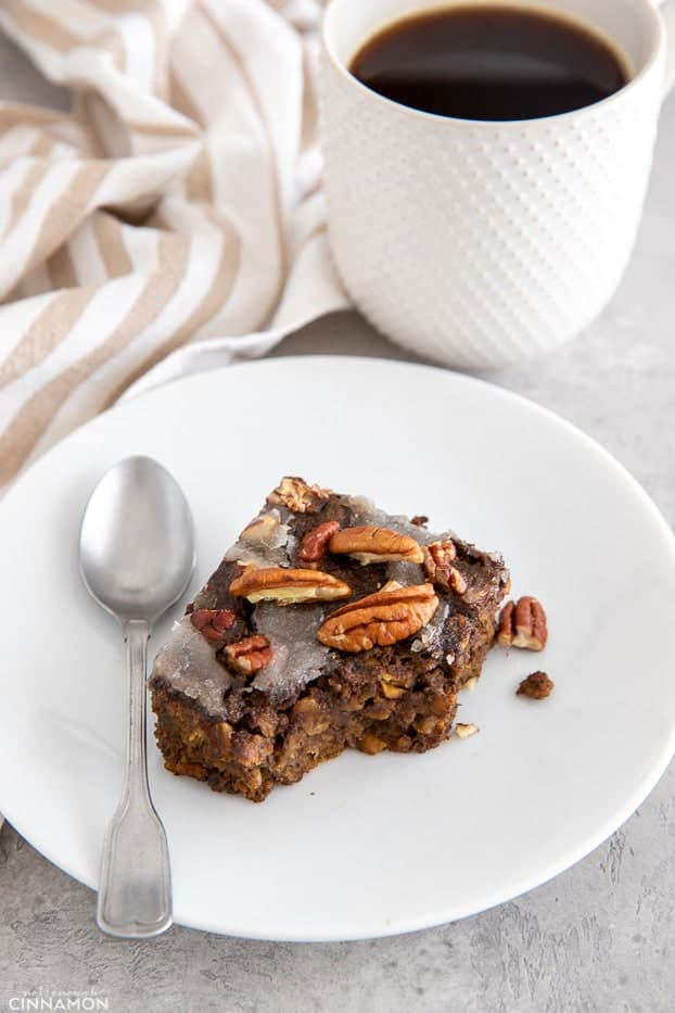 a square of vegan gingerbread baked oatmeal with a spoon on the side