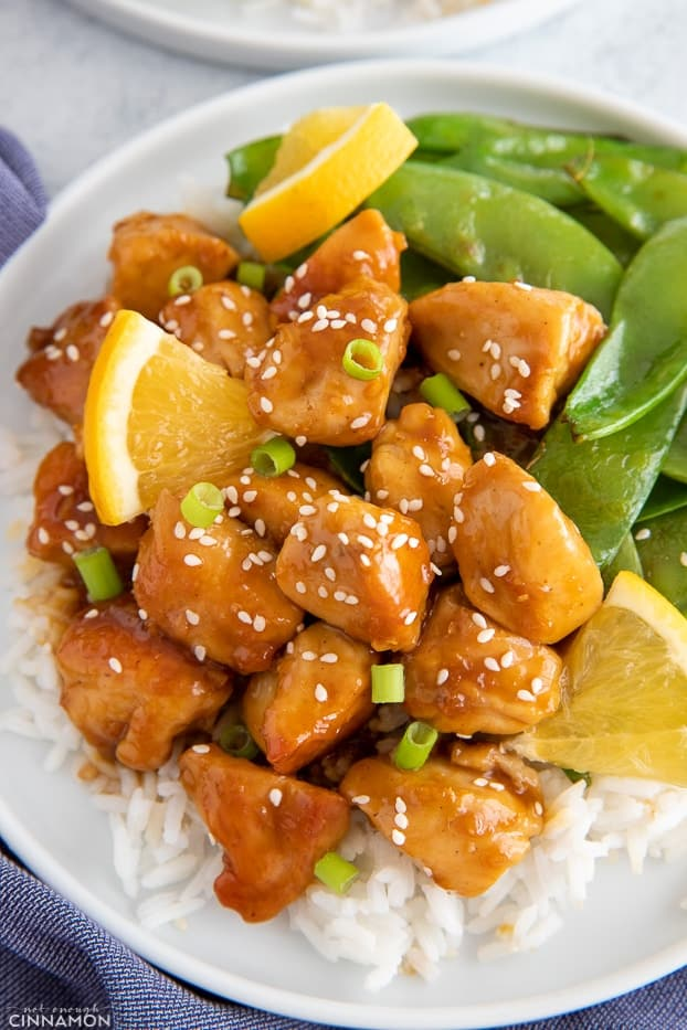 Chinese restaurant style sticky orange chicken served over a bed of rice with a side of snow peas