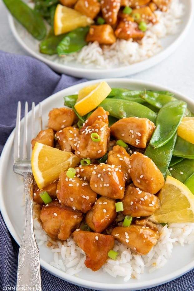 sticky one skillet orange chicken served over rice with a side of snow peas
