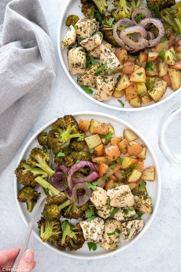 overhead shot of two plates of sheet pan ranch chicken served with baked veggies