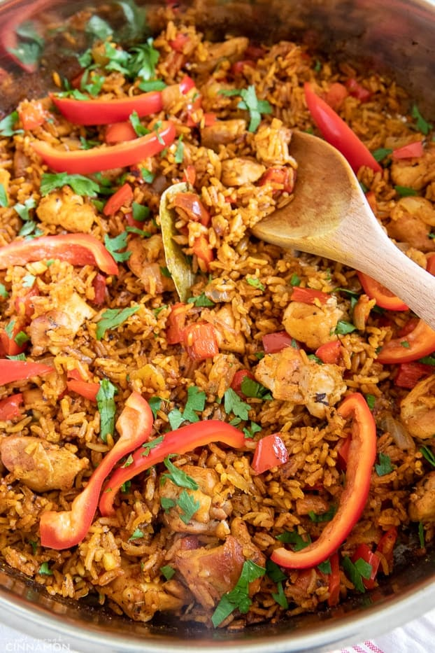 a wooden spoon stirring in a pot of homemade West African Jollof chicken and rice
