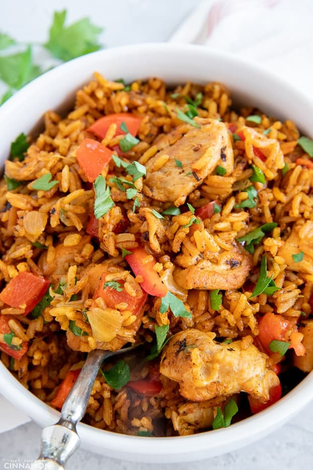 close up of a bowl of West African healthy Jollof rice with chicken sprinkled with cilantro