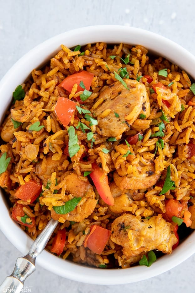 a serving of healthy African Jollof Rice with chunks of chicken and red bell pepper