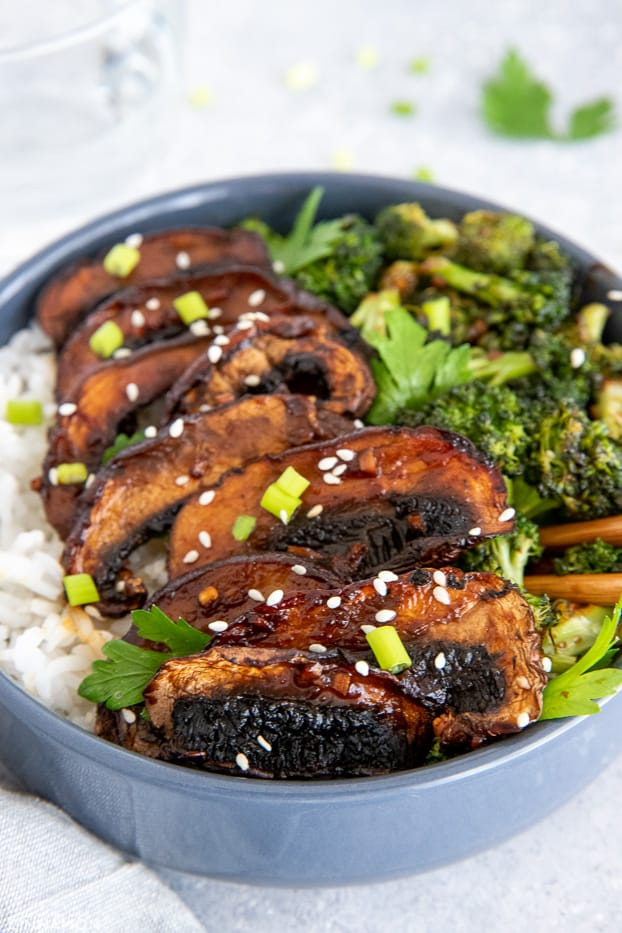 glazed teriyaki mushrooms served on rice in a bowl with chopsticks on the side
