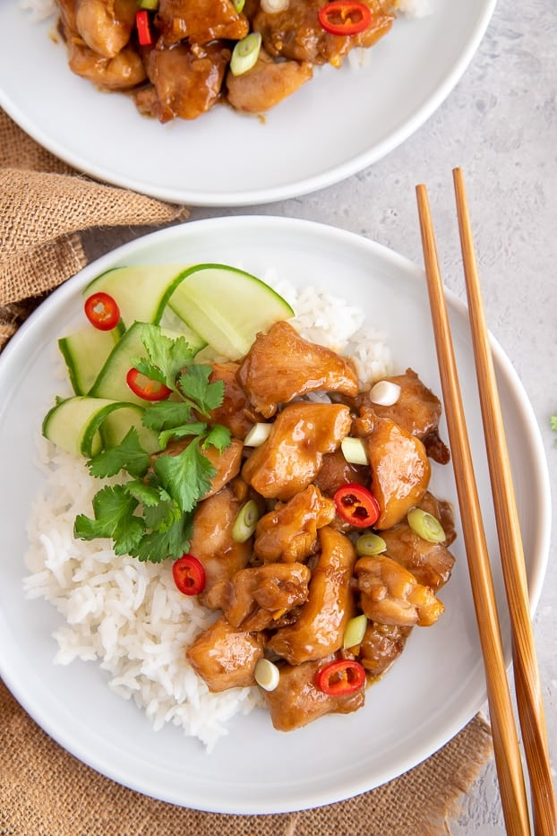 a serving of coconut caramel chicken with rice and cucumber salad with chopsticks on the side