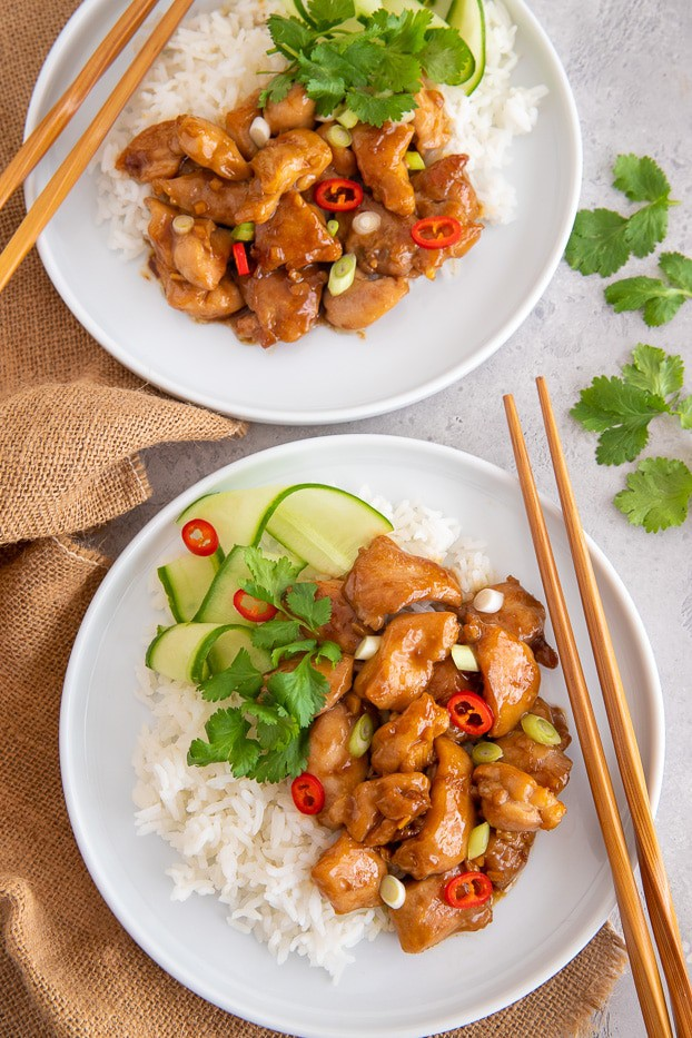 two servings of coconut caramel chicken served with rice and cucumber salad