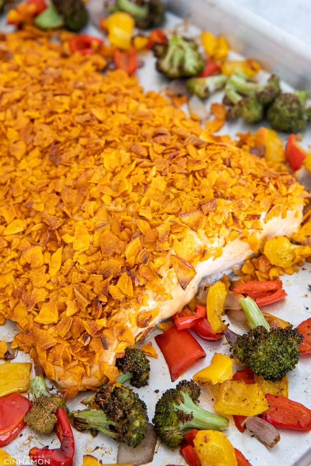 salmon fillet baked with a crust of crushed sweet potato chips surrounded by baked vegetables