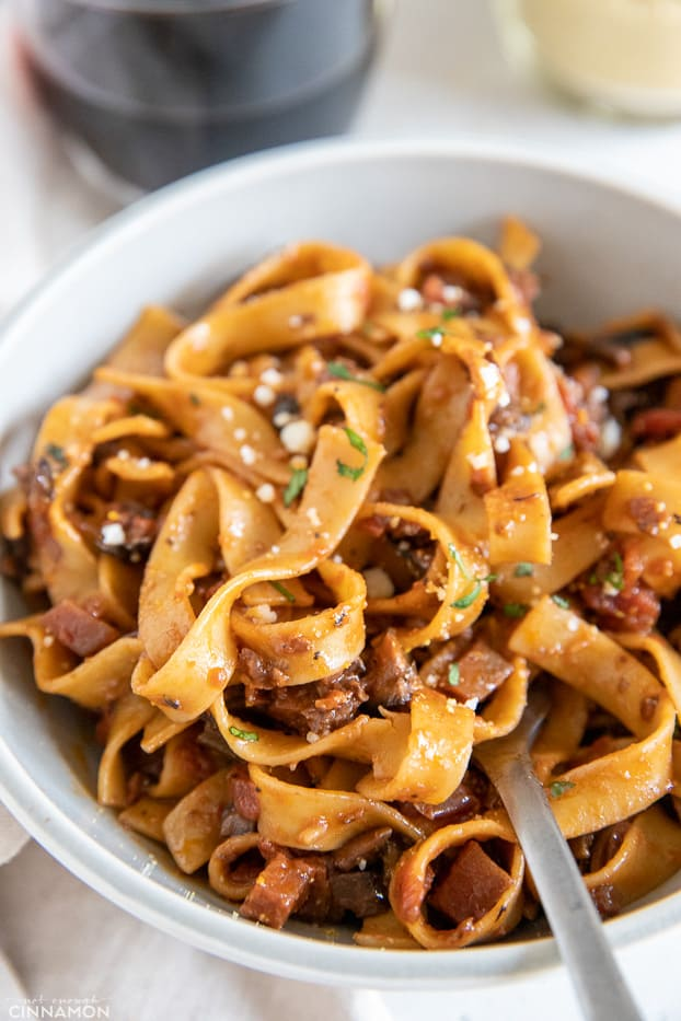 a fork twirling fettuccine pasta with mushroom bolognese and vegan parmesan